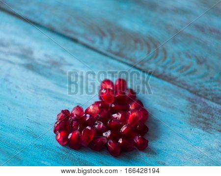 Heart made of pomegranate seeds on old wooden table, side view. Mothers day background.