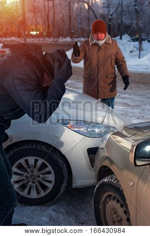 Two upset men after car crash on city street. Male drivers examining cars after collision.