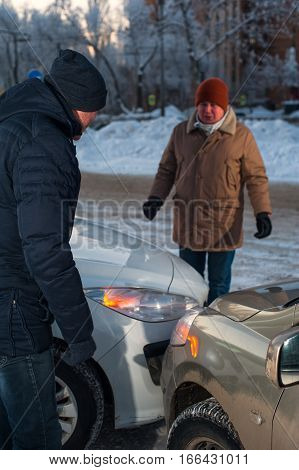 Two caucasian drivers arguing after car crash. Men looking at damaged auto.