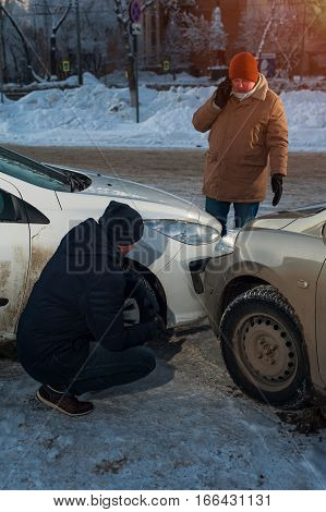Two upset male drivers looking at damaged cars after crash. Man calling to car assistance service. Winter time