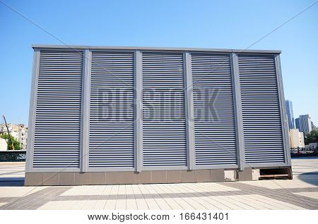 Close up on Industrial air conditioning and ventilation systems on the street against cloudy sky. Ventilation system of factory outdoor.