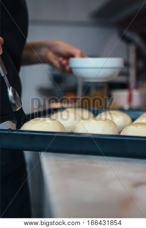 Close-up of unrecognizable woman brushing buns with butter - Focus on the brush