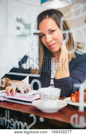Portrait of smiling woman looking at camera while sitting in cafe with cell and organizer