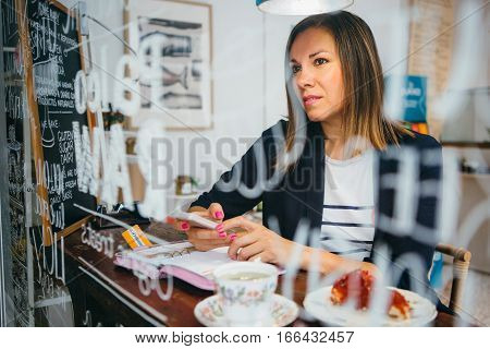Portrait of brunette looking away while holding cell at table in cafe
