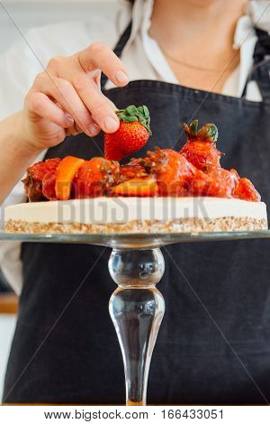 Unrecognizable confectioner decorating cake with strawberry on cake stand