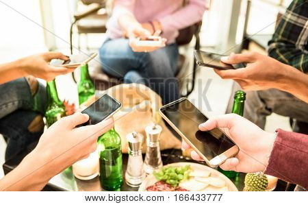Group of multicultural friends having fun on smartphone at bar - People hands using mobile smart phone - Technology concept with addicted men and women - High iso image with shallow depth of field
