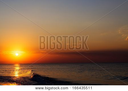 bright yellow golden sunset with reflection in sea surface with waves
