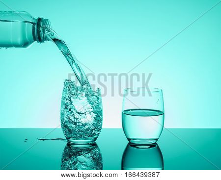 Bottle with creative splashing water in the glass on turquoise background.
