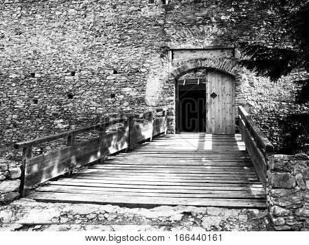 Entrance wooden bridge and gate of medieval stronghold Kasperk Castle near Kasperske Hory in Southern Bohemia, Sumava Mountains, Czech Republic, Europe.