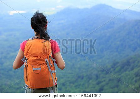 young female traveler with backpack standing on the mountain peak
