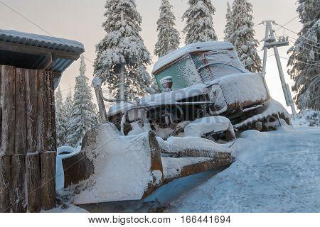 Snowbound bulldozer standing near a barn in the background is seen the dawn. Mountain Dragobrat Western Ukraine.