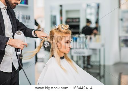 Hairstylist is drying long blond hair of his client. Focus on worker and a client