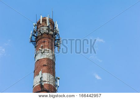 brick chimney with equipment for cellular communication on a sky background