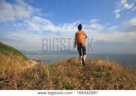 successful female hiker hiking on seaside mountain peak