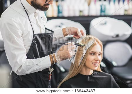 Professional hairdresser is working with a client. He is dying hair