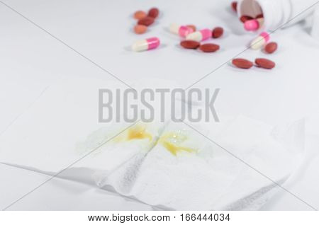 The Yellow And Green Snot On White Tissue Paper With Pill. Cold Sick