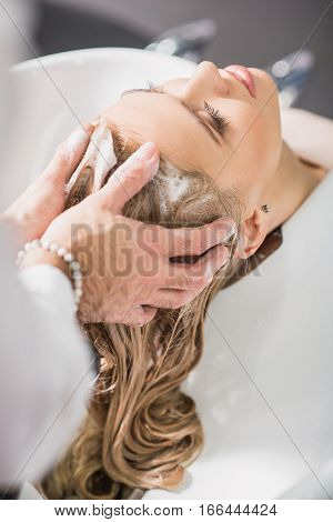 Calm young woman is enjoying the procedure at beauty salon. Stylist is washing her hair