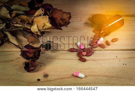The Pill Spilling Out Of Brown Color Pill Bottle With Dried Rose Flower On Wooden Background. Fail I