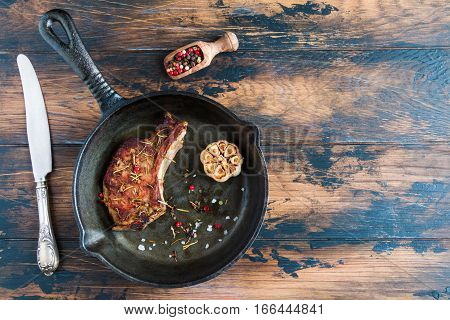 Rib eye pork steak and baked garlic in black cast-iron skillet on wooden rustic table. Red pepper vintage knife top view.