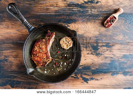 Rib eye pork steak and baked garlic in black cast-iron skillet on wooden rustic table. Red pepper top view.
