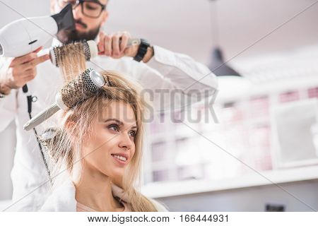 Young woman is smiling while sitting at the hairdresser salon. stylist is combing her hair