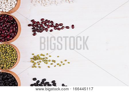 Assortment of haricot in a wooden bowls with copy space and tracks beans on white wood background. Top view closeup. Healthy protein food.