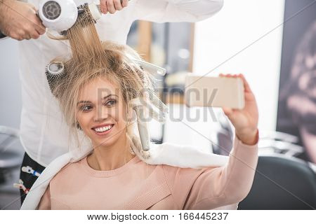 Young lady is taking pictures of her hairdo. She is sitting at beauty salon and holding smartphone