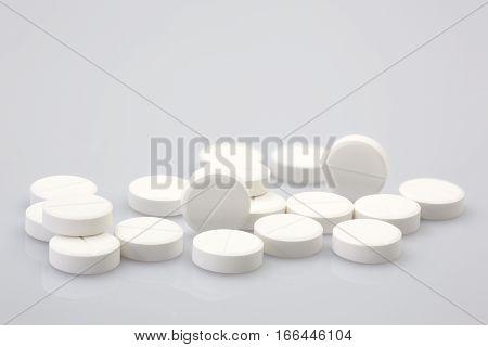 Group of white medical pills closeup shot