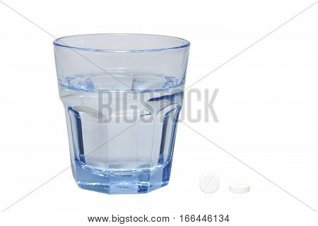 Single tablet and a glass of water isolated on white