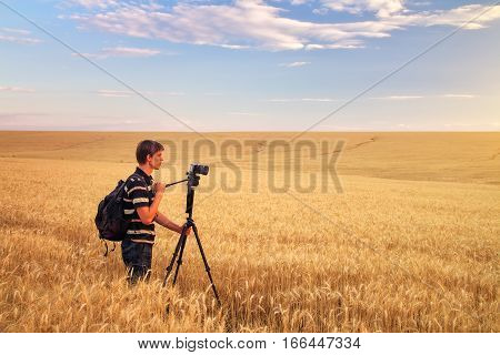 Photographer takes pictures in a wheat field. The man with the camera in a field at sunset. Man working in nature.