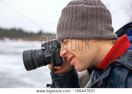 Closeup of photographer with digital camera outdoors. Beautiful young man photographs nature.