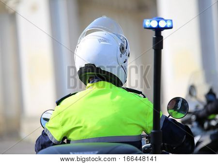 Police Officer On Motorcycle With Flashing Blue Siren In The Cit