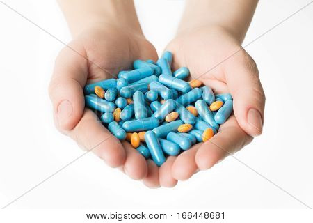 Hands Is Giving Blue Capsules And Orange Pills On White Background.