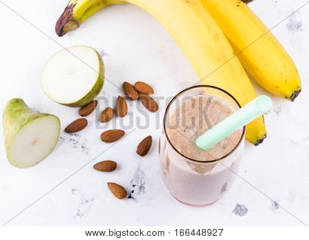 Healthy breakfast. Banana strawberry and apple smoothie in glass with fresh bananas pear and almond nuts on white marble table. Selective focus.