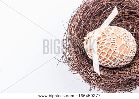 Easter egg in handmade knitted bag in brown nest. Selective focus.