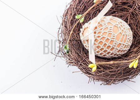 Spring easter egg in handmade knitted bag in brown nest with spring decor. Selective focus.