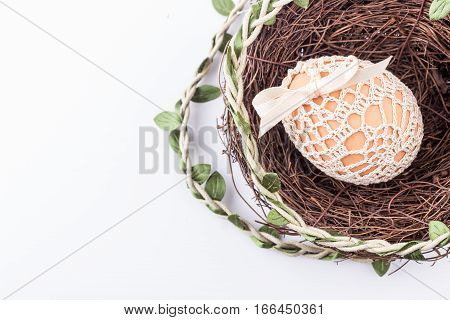 Holiday easter egg in knitted bag in nest with easter decor. Selective focus.