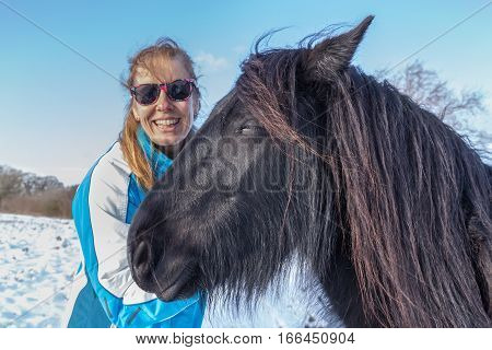 Portrait caucasian woman with frisian horse in winter snow