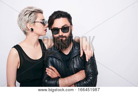 young happy couple of blond woman with short hairstyle and handsome bearded man wearing leather rock jacket on white background