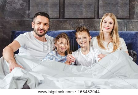 Happy family lying in bed under grey duvet