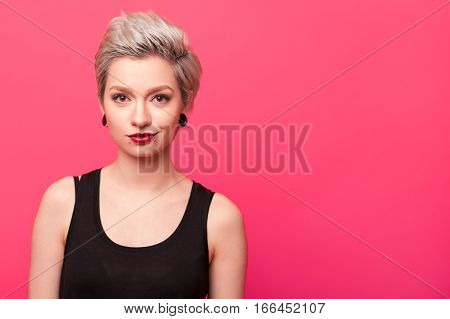Shoulders close-up portrait of beautiful young woman smiling with perfect makeup and dyed blond hair. blonde model girl face over pink color background with copy space. Short hairstyle