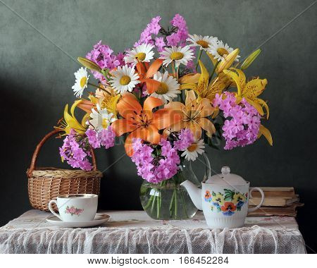 country still life with a bouquet of lilies and utensils for tea on the table with a retro tablecloth.