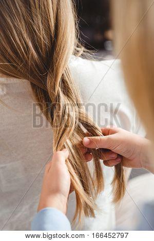 Close-up partial view of little daughter plaiting braid of her mother