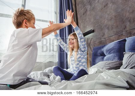 Cute smiling siblings in pajamas playing on bed