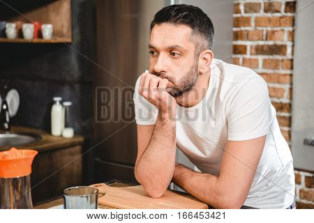 Thoughtful man leaning on kitchen table and looking away