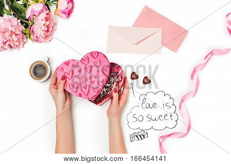The female hands with rose, gift box, ribbon, hearts and blank sheet of paper and pen on white background. The happy Valentine's Day concept