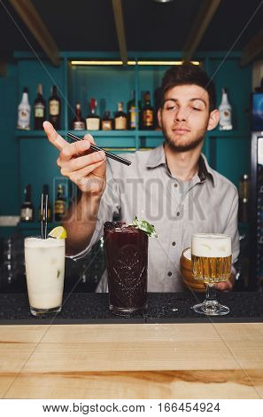 Young handsome Barman offers exotic sweet cocktails in restaurant. Professional bartender at work in night club bar made refreshing drinks. Selective focus on glasses