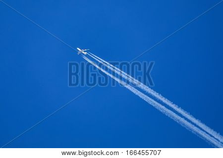 big airliner on clear blue sky with with white line of engines