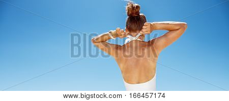 Seen From Behind Woman Tying White Swimsuit At Sandy Beach