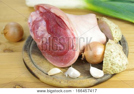 raw knuckle of pork on wooden board